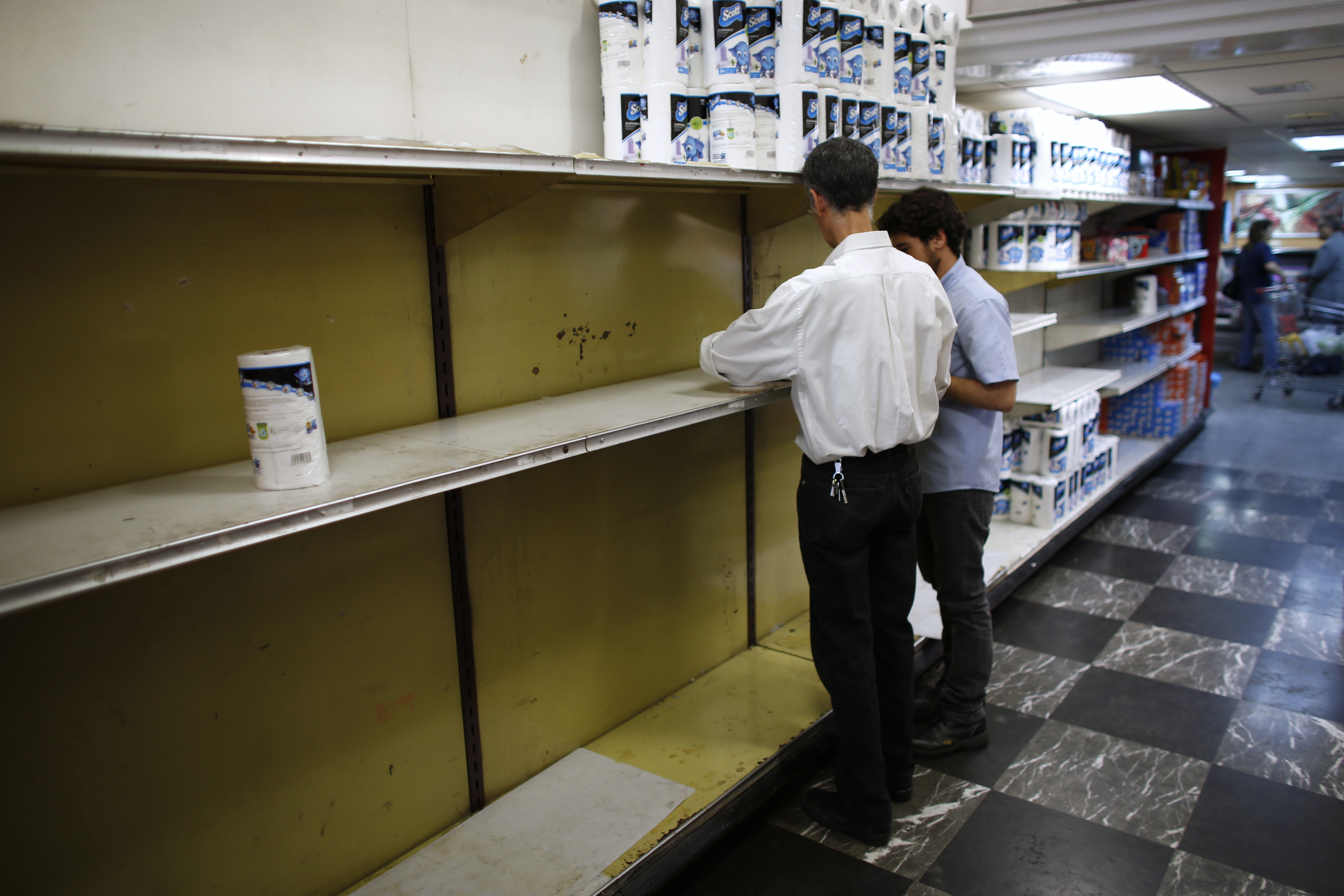 "Supermarket staff work next to partially empty shelves of toilet paper in Caracas May 16, 2013. Supplies of food and other basic products have been patchy in recent months, with long queues forming at supermarkets and rushes occurring when there is news of a new stock arrival. The situation has spawned jokes among Venezuelans, particularly over the lack of toilet paper. The government announced this week it was importing 50 million rolls to compensate for ""over-demand due to nervous buying."" REUTERS/Jorge Silva (VENEZUELA - Tags: POLITICS BUSINESS) - RTXZPIP"